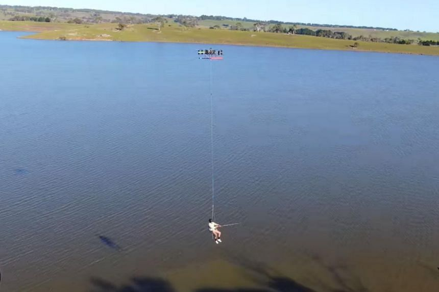 The video shows a man in a seat hanging by rope from an armchair-sized drone several metres above a lake in the state of Victoria.
