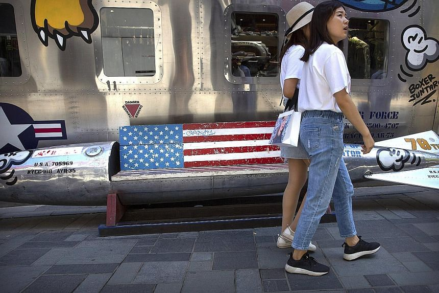 Shoppers walking past a missile-shaped bench painted like a US flag outside a clothing store in Beijing. In a survey by the US-China Business Council, 40 per cent of respondents said they have lost out on sales in China due to their Chinese partners'