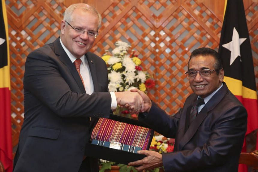 Australian Prime Minister Scott Morrison receiving a souvenir of traditional Timorese woven cloths from East Timorese President Francisco Guterres during their meeting in Dili on Aug 30, 2019.