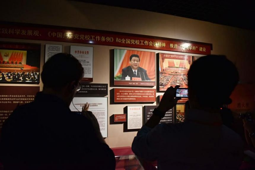 A photo taken on June 26 shows journalists filming a display featuring Chinese President Xi Jinping in the history museum at the Party School of the Chinese Communist Party's Central Committee in Beijing.