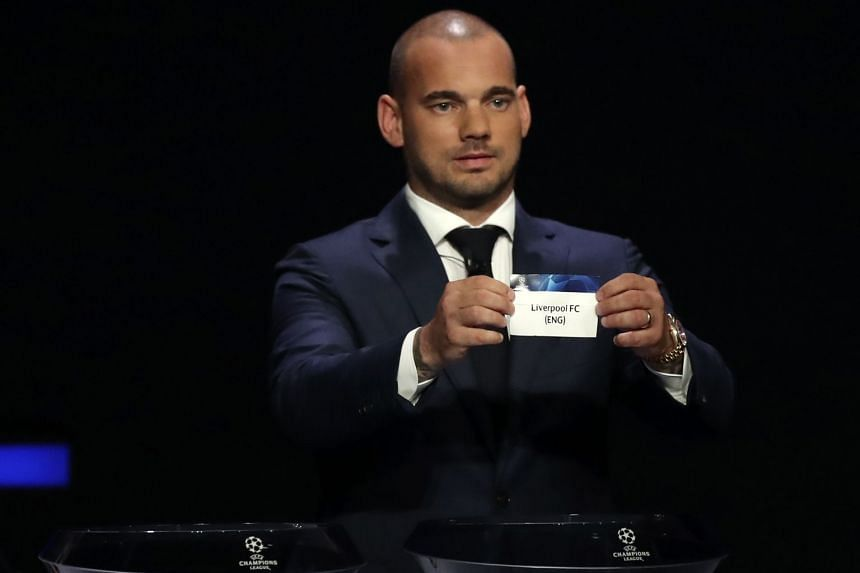 Former Dutch soccer player Wesley Sneijder shows the name of Liverpool during the group stage draw.