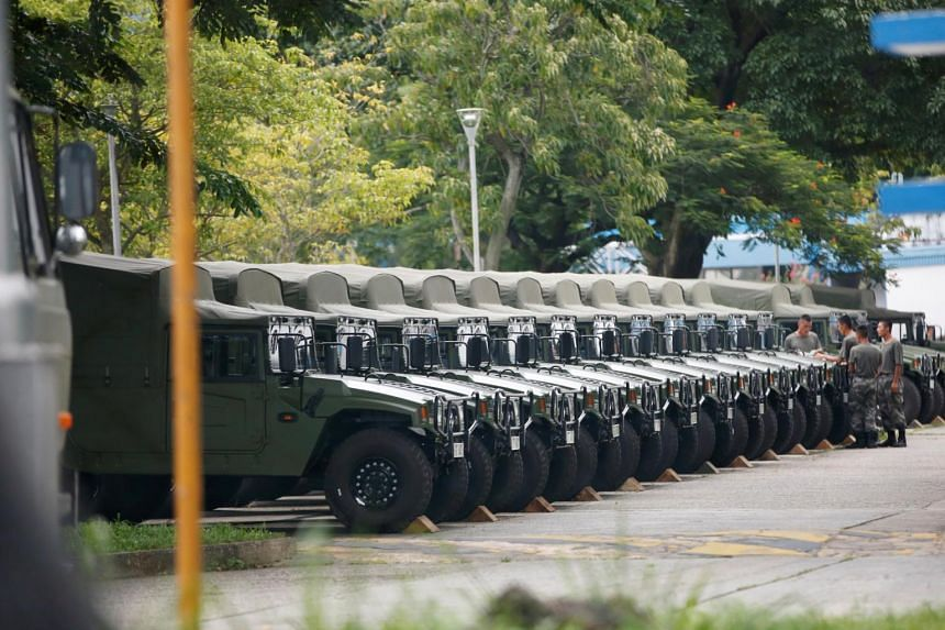 Troops are seen by a row of over a dozen army jeeps at the Shek Kong military base of People's Liberation Army (PLA) in New Territories, Hong Kong on Aug 29, 2019.