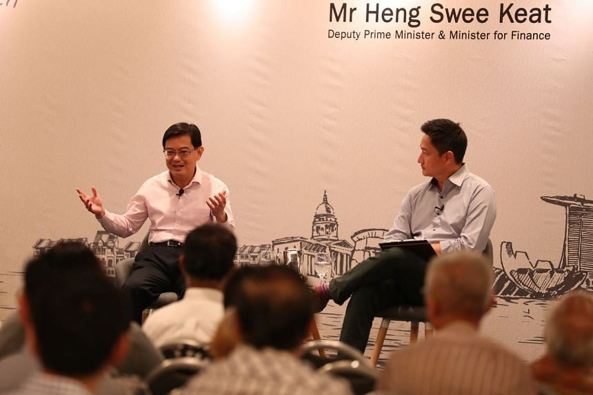 Deputy Prime Minister and Minister of Finance Mr Heng Swee Keat (left) sharing his opening remarks before the dialogue as moderator Steven Chia (right) looks on.