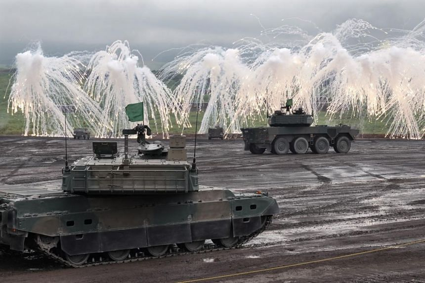 Type 10 tanks, Type 90 tanks and armored vehicles fire munitions during a fire drill conducted by elements from Japan's Ground Self-Defence Force at the Higashi-Fuji training field in Gotemba, central Japan, on Aug 22, 2019.