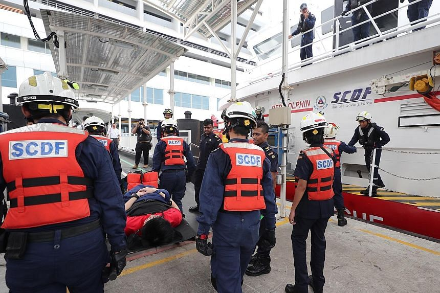 A passenger being brought down on a stretcher from a Singapore Civil Defence Force marine rescue vessel during the exercise yesterday. ST PHOTO: GAVIN FOO