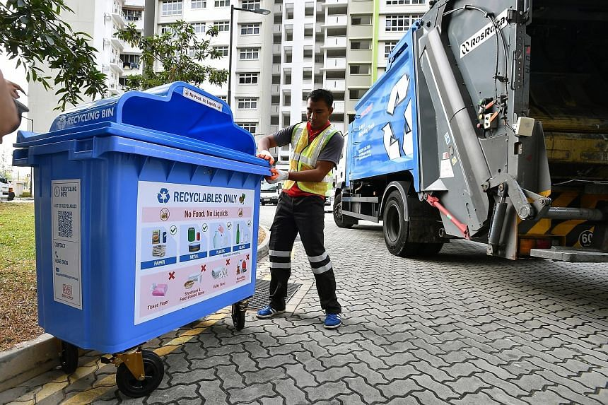 Recycling truck attendant Mohamat Hadilusandy Abdul Hadi, 26, with a bin bearing the new label, which prominently states that no food or liquids are allowed in the recycling bin. Achieving the target of reducing waste sent to the offshore Semakau Lan