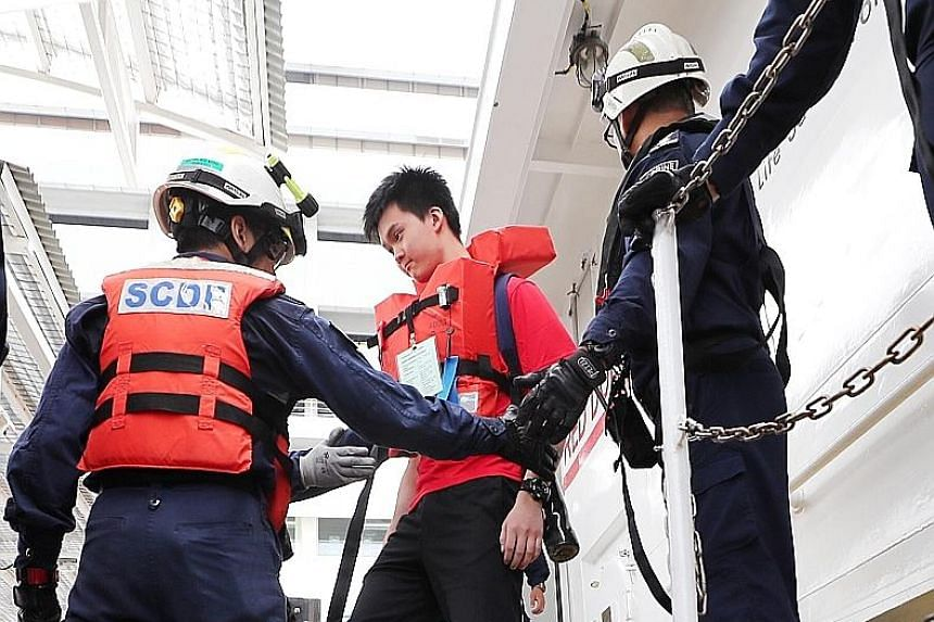 Passengers (above) disembarking from an SCDF Heavy Rescue Vessel at the HarbourFront Ferry Terminal during an exercise held yesterday that simulated the evacuation of 150 passengers on board a regional ferry involved in a collision in the waters sout