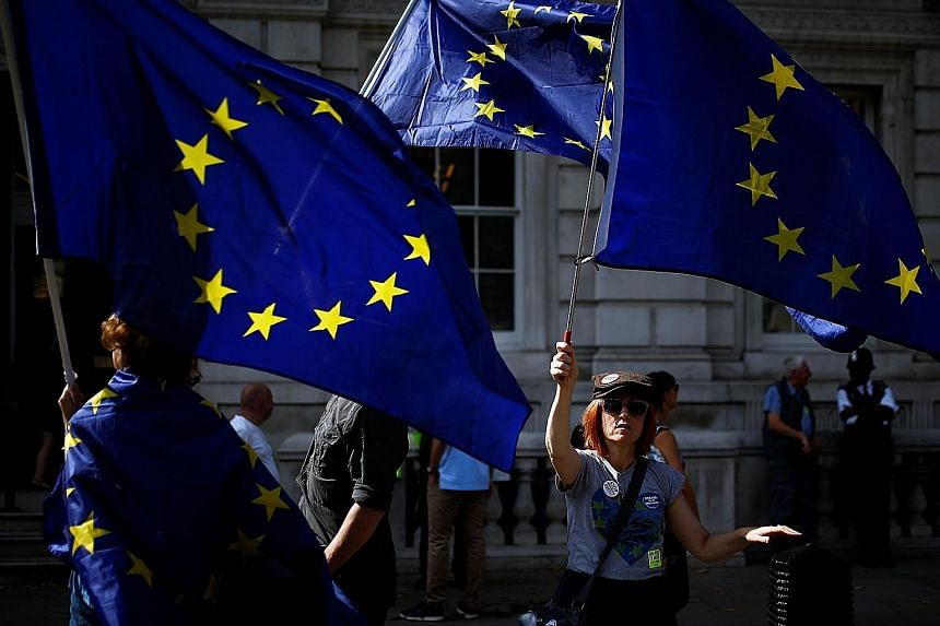 Anti-Brexit protesters waving European Union flags outside the Cabinet Office in London yesterday. Britain's negotiators are to meet their EU counterparts throughout next month in a bid to reach a new divorce deal.