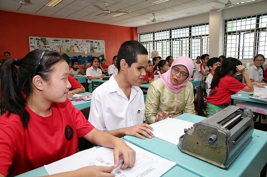 President Halimah Yacob interacting with visually impaired Secondary 2 student Lawrence Gabriel V. Angel, 15, in a geography class during her visit to Ahmad Ibrahim Secondary School yesterday. Next to Lawrence is Secondary 2 student Goh Si Ying, 14,