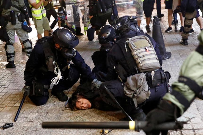 A demonstrator being detained by police officers during a protest in Hong Kong, on Aug 31, 2019.