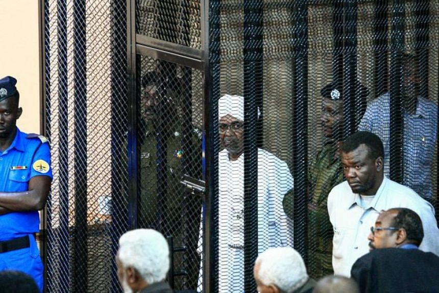 Sudan's ousted president Omar al-Bashir appeared in court in a black metal cage wearing the country's traditional white attire and turban.