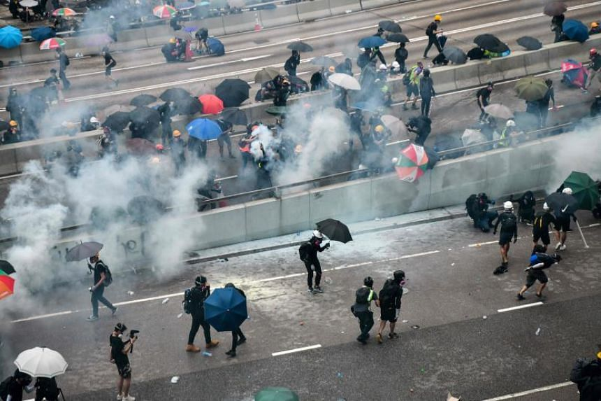 Protesters react after police fire tear near the government headquarters of Hong Kong, on Aug 31, 2019.