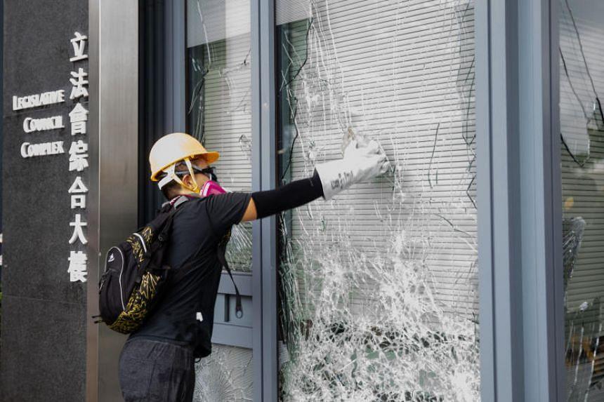 A demonstrator breaks a glass window outside Hong Kong's Legislative Council on Aug 31, 2019.