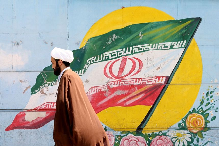 An Iranian cleric walks past a mural painting of the national flag.