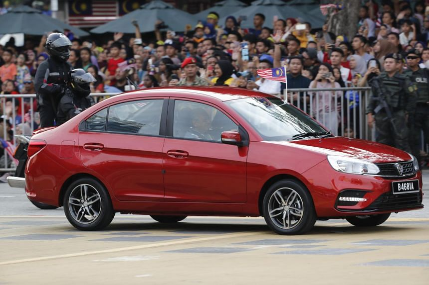 PM Mahathir Mohamad was seen driving a maroon Proton Saga to the main stage.