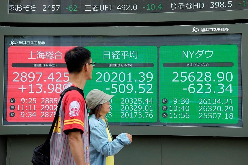 Stock quotation boards in Tokyo last Monday showing prices on the stock exchanges of (from left) Shanghai, Tokyo and New York. The writer cites history to show that the longer you hold your equities portfolio, the higher the probability that it would