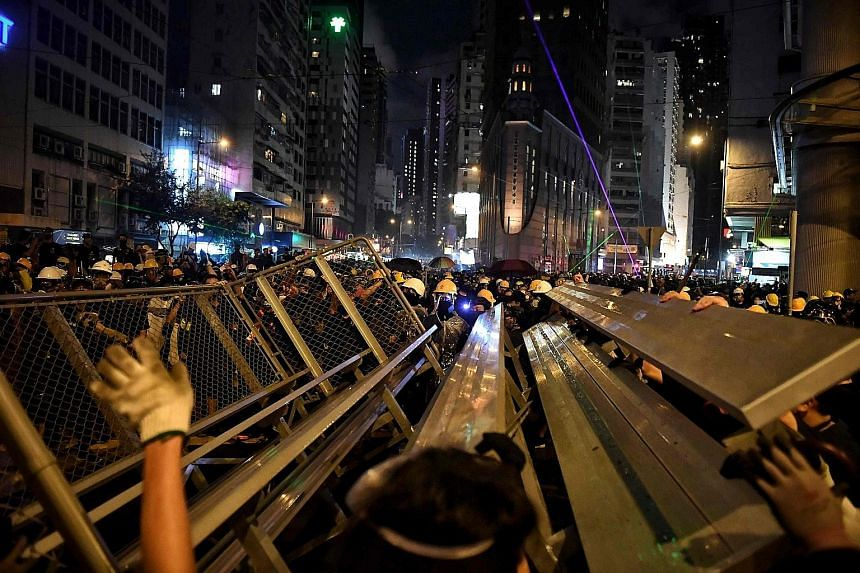 Above: Protesters building a barricade in Hennessy Road in Hong Kong yesterday, in the latest opposition to a planned extradition law that has since morphed into a wider call for democratic rights in the semi-autonomous city. They have taken to the s