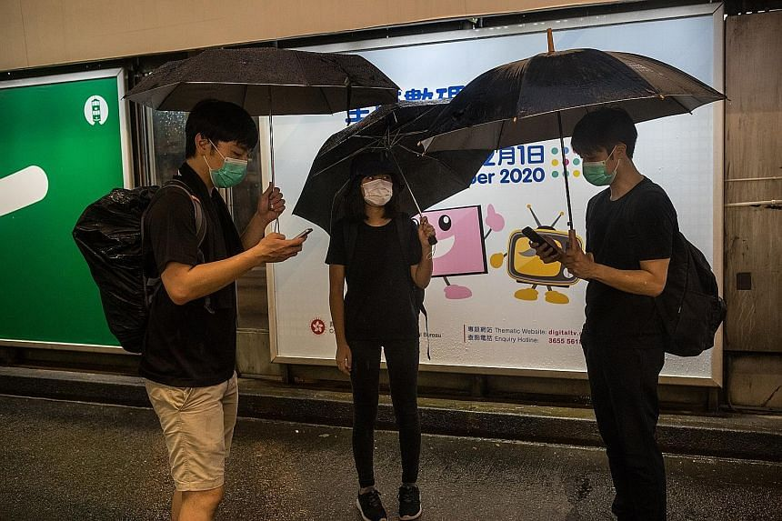 Some friends checking the Telegram message boards to see where other protesters are. Hong Kong protesters use encrypted apps to mobilise swiftly through multiple group chats.