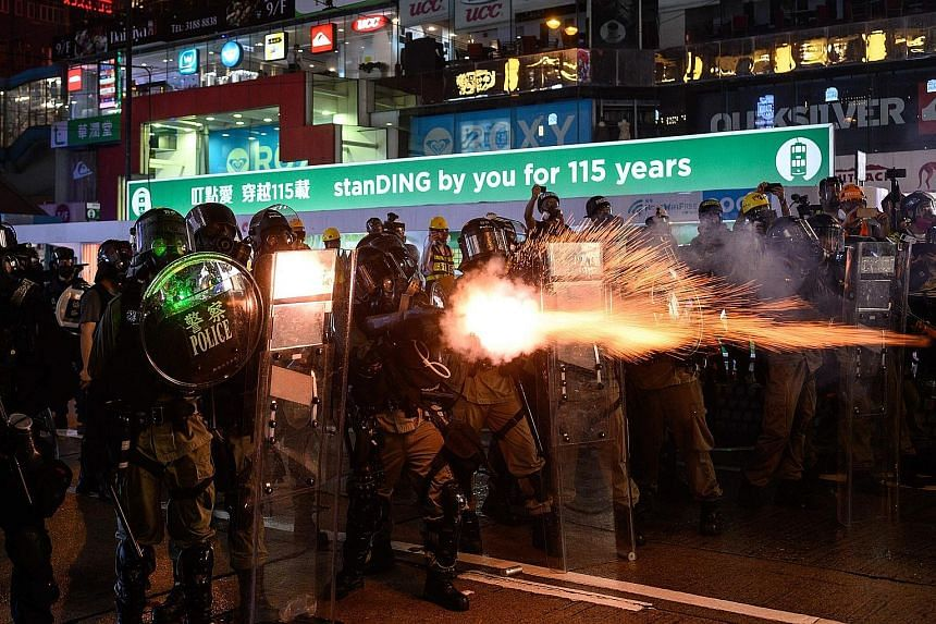 A protester hurling back an exploded tear gas shell, as the police shot blue-coloured water from water cannon in central Hong Kong yesterday. Thousands of demonstrators marched in the muggy weather armed with umbrellas.