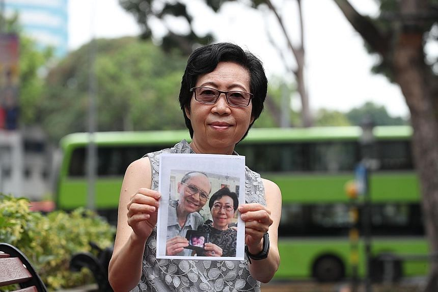 Mrs Carol Lye holding a photograph of herself and her late husband Caesar Lye, who helped dozens of people in need over many years. ST PHOTO: TIMOTHY DAVID