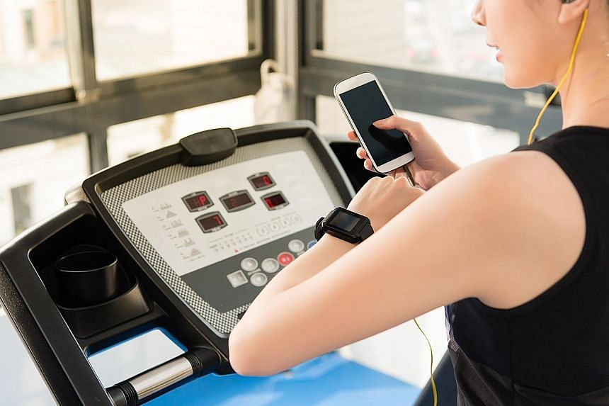 While technology can be helpful to our exercise regimen, like this woman who tracks her progress on the treadmill on her smartwatch while listening to music on her smartphone, it is beneficial to disconnect oneself from the digital realm regularly to