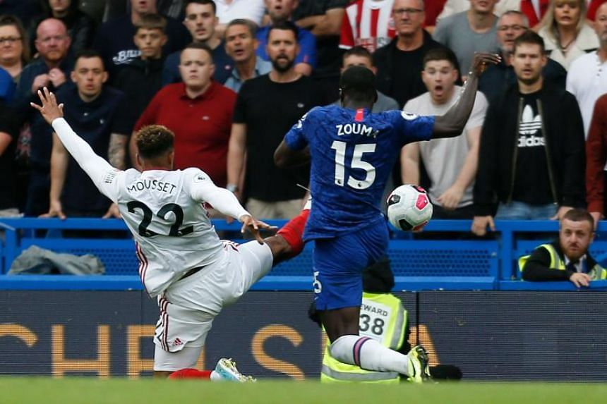 Sheffield United's French striker Lys Mousset (left) stretches for the ball that comes off Chelsea's French defender Kurt Zouma for an own goal to equalise for Sheffield 2-2 in London on August 31, 2019.