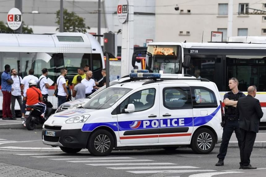A police officer stands guard as people gather in Villeurbanne on the outskirts of Lyon in south-eastern France on Aug 31, 2019, after a knife attack which has left one dead and six injured.