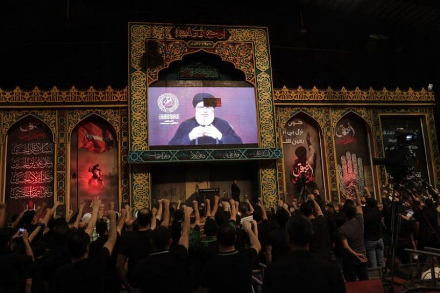 Supporters of the Lebanese Shiite Hezbollah movement gather to watch the transmission on a large screen of a speech by the movement's leader Hasan Nasrallah on Aug 31, 2019.