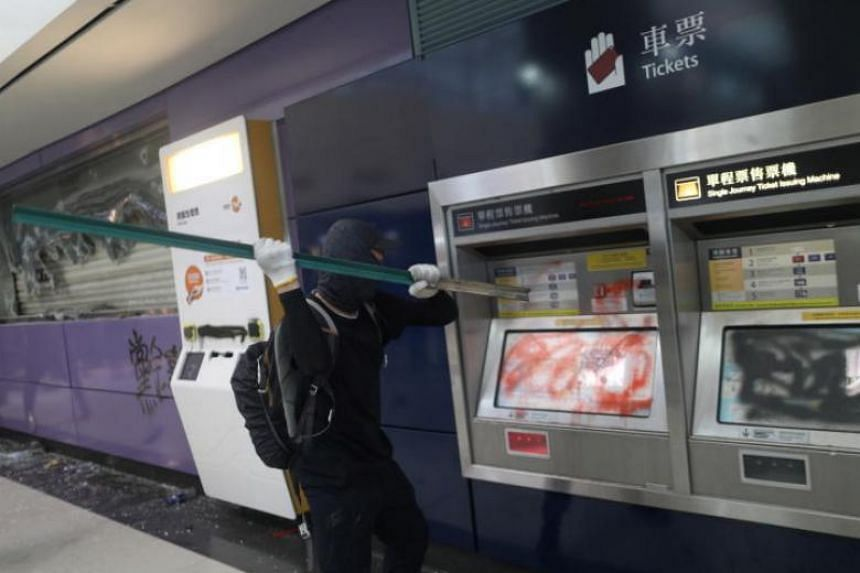 A protester smashes ticket machines at the Tung Chung MTR station in Hong Kong on Sept 1.