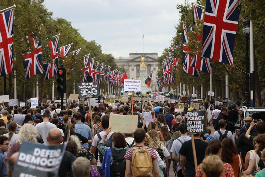 Protesters hold placards during an anti-Brexit protest against UK Prime Minister Boris Johnson's decision to suspend Parliament on Aug 31, 2019.