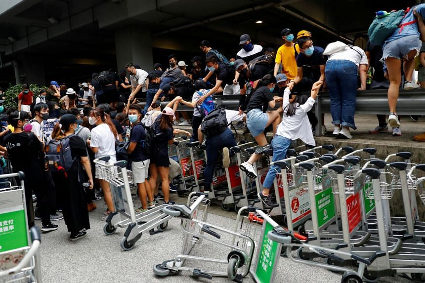 Protesters run away from the riot police outside the terminals at Hong Kong International Airport on Sept 1, 2019.