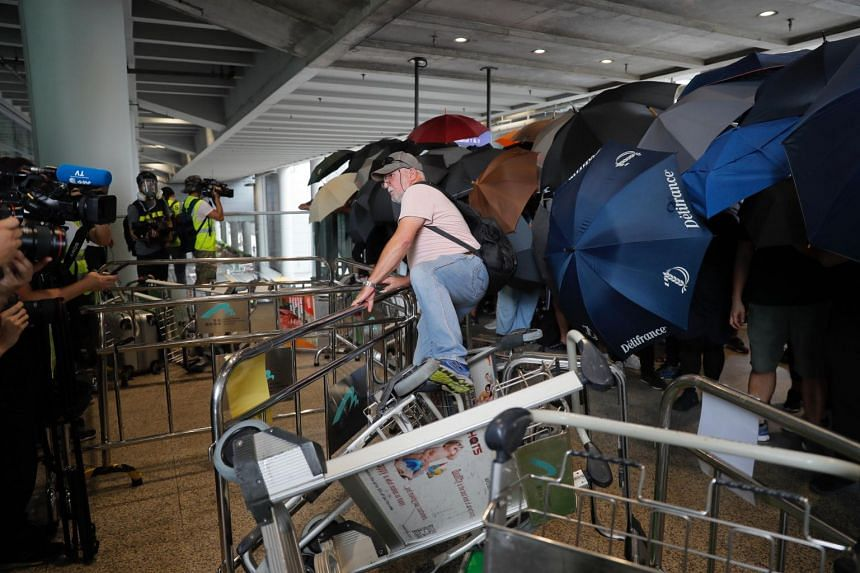 A passenger climbs over barriers as pro-democracy protesters block entrances outside the Hong Kong airport on Sept 1, 2019.