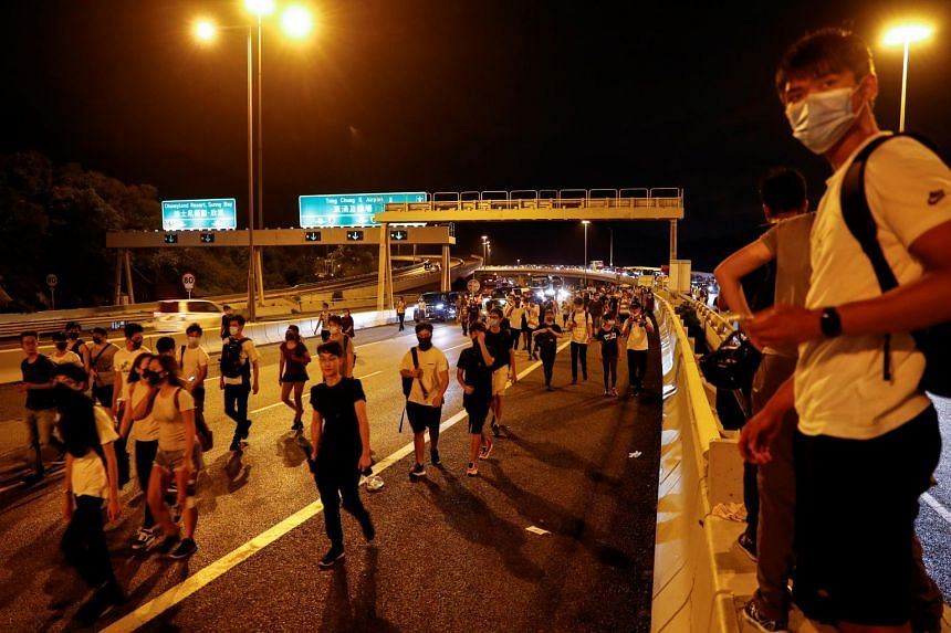 Protesters walk among the traffic on the highway leading to Hong Kong International Airport after a day of protests on Sept 1, 2019.