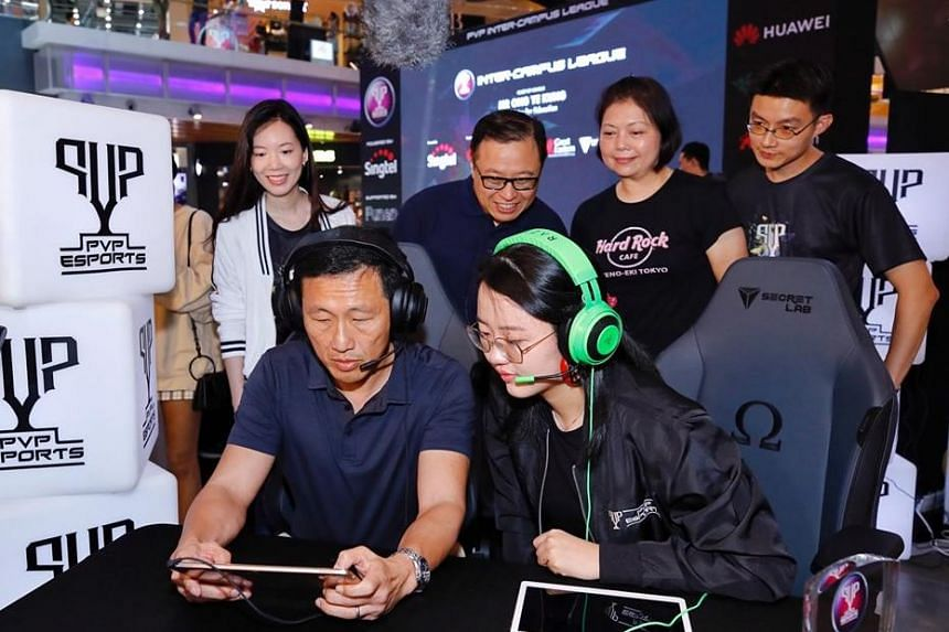 Education Minister Ong Ye Kung learns the ropes of Mobile Legends: Bang Bang from one of the players in Team GPA 6.0.