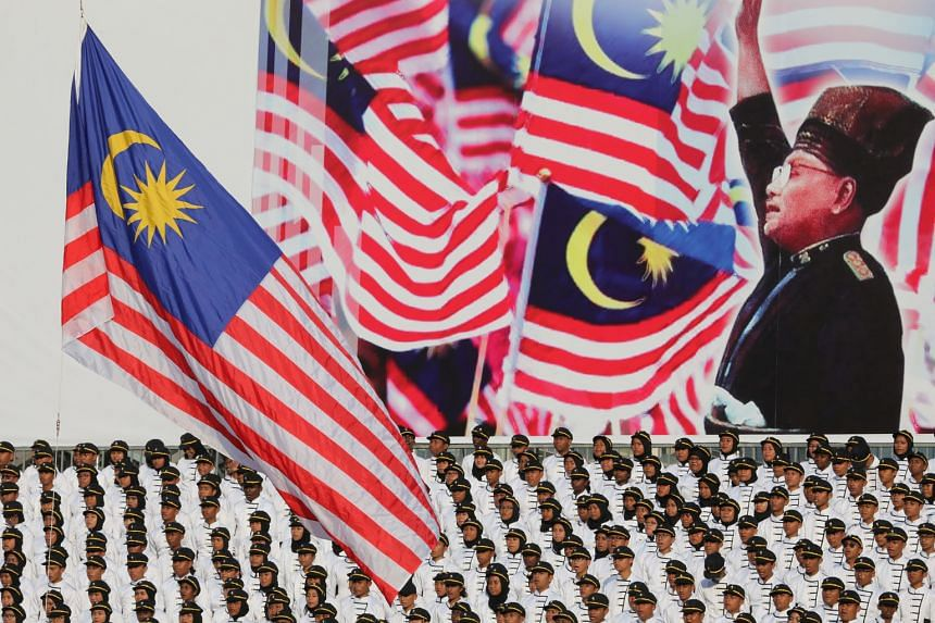 Performers singing Malaysia's national anthem during celebrations to mark the 62nd anniversary of the country's independence in Putrajaya yesterday, against a backdrop featuring the country's first prime minister, Tunku Abdul Rahman.