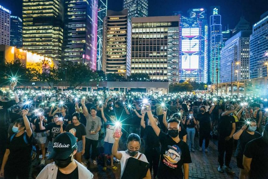 In a photo from Aug 22, 2019, secondary school students raise their phone torches during a rally at Edinburgh Place in Hong Kong.