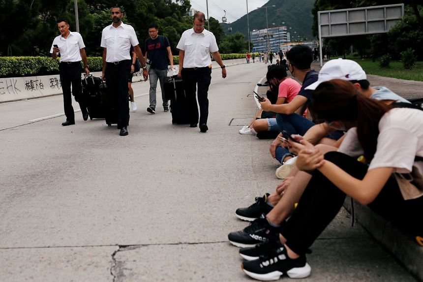 Pilots try to get to the airport as anti-extradition bill protesters block the highway leading to it, in Hong Kong.