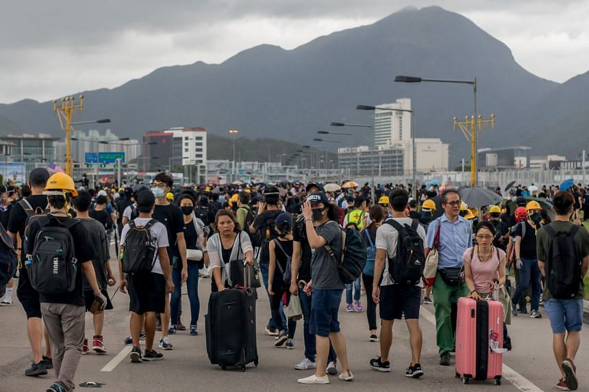 Passengers walk with their luggage as protesters block the roads leading to Hong Kong International Airport.