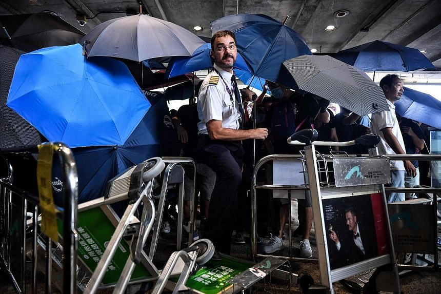 Far left: An airline crew member trying to make his way through a makeshift barricade made by protesters using luggage trolleys at Hong Kong International Airport yesterday. Left: The makeshift barricade. PHOTO: REUTERS An anti-government protester t
