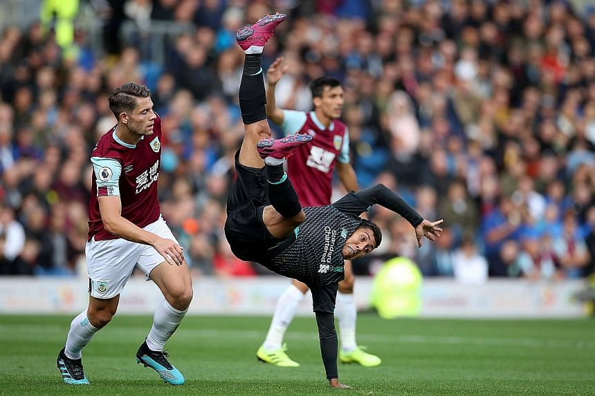 Liverpool's Roberto Firmino resorts to acrobatics in an attempt to beat Burnley's James Tarkowski to the ball. The Reds won the Premier League game 3-0 at Turf Moor on Saturday. PHOTO: REUTERS