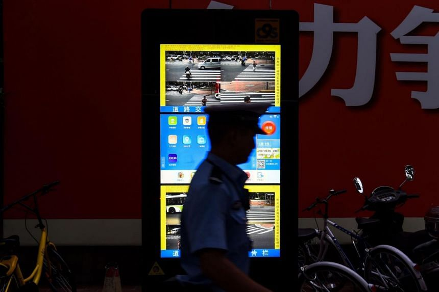 In a photo taken on Aug 9, 2017, a traffic policeman walks past a facial recognition screen at a road intersection in Shanghai.