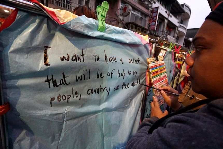 In a photo from March 2016, a woman from the Solomon Islands writes her well wishes on a lantern before releasing it during the Pingxi Sky Lantern Festival 2016, in Shifen Sky Lantern Square, New Taipei City, north of Tainan.