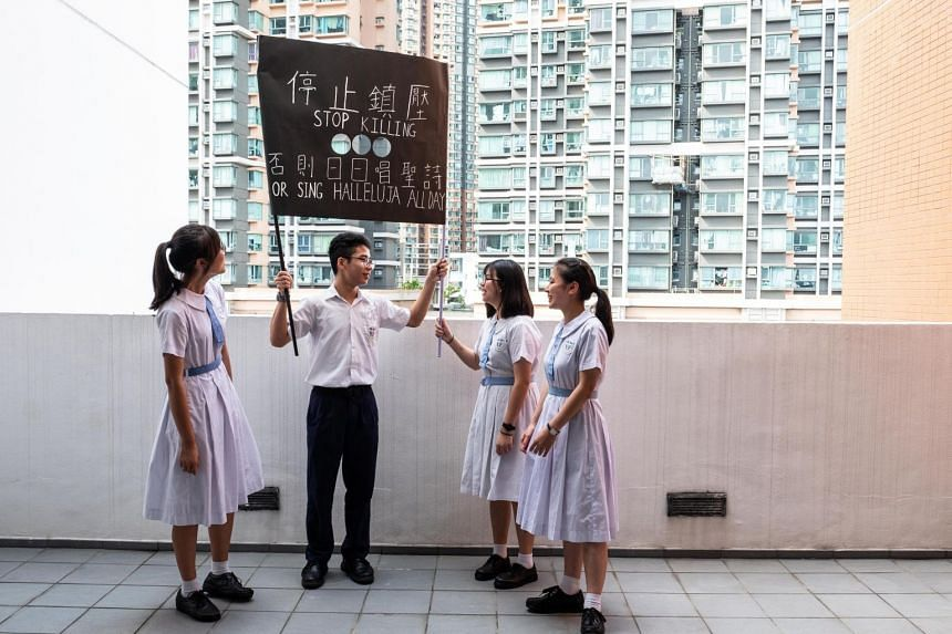 A photo from July 12, 2019 shows students with a protest banner at their school in Lai Chi Kok, Hong Kong. Pro-Beijing supporters say the prominence of the city's youngsters at recent protests is a clear sign that academic freedom has gone too far, g