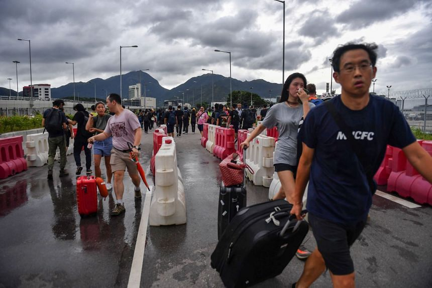People walk through barriers set up by protesters on a road near Hong Kong International Airport.