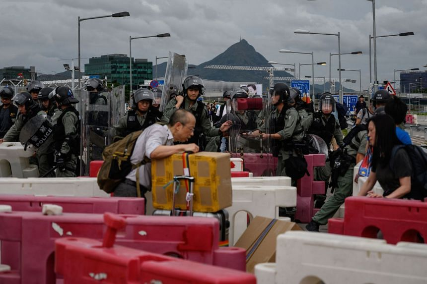 Police clear barricades set up on a road by protesters as passengers walk with their luggage to Hong Kong International Airport.