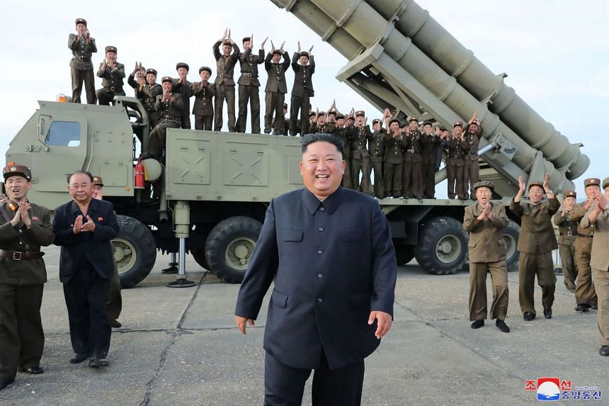 """An Aug 24, 2019 photo shows North Korean leader Kim Jong Un (centre) celebrating the test-firing of a """"newly developed super-large multiple rocket launcher"""" at an undisclosed location."""