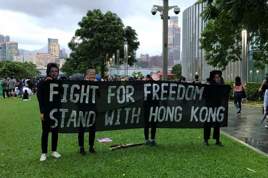 """Protesters donning masks of Donald Trump, Justin Trudeau, Emmanuel Macron and Shinzo Abe chanting """"fight for freedom, stand with Hong Kong!""""."""