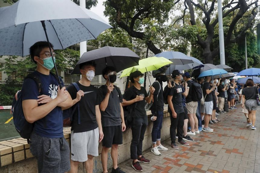 Current and former students stand outside their secondary school for a protest in Central in Hong Kong on Sept 2, 2019.