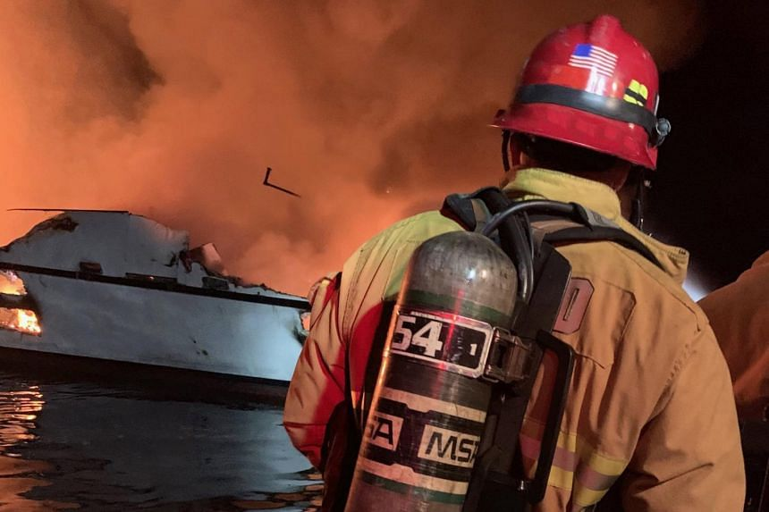 Firefighters attempt to extinguish a fire on a boat off the coast of Santa Cruz Island, California, on Sept 2, 2019.