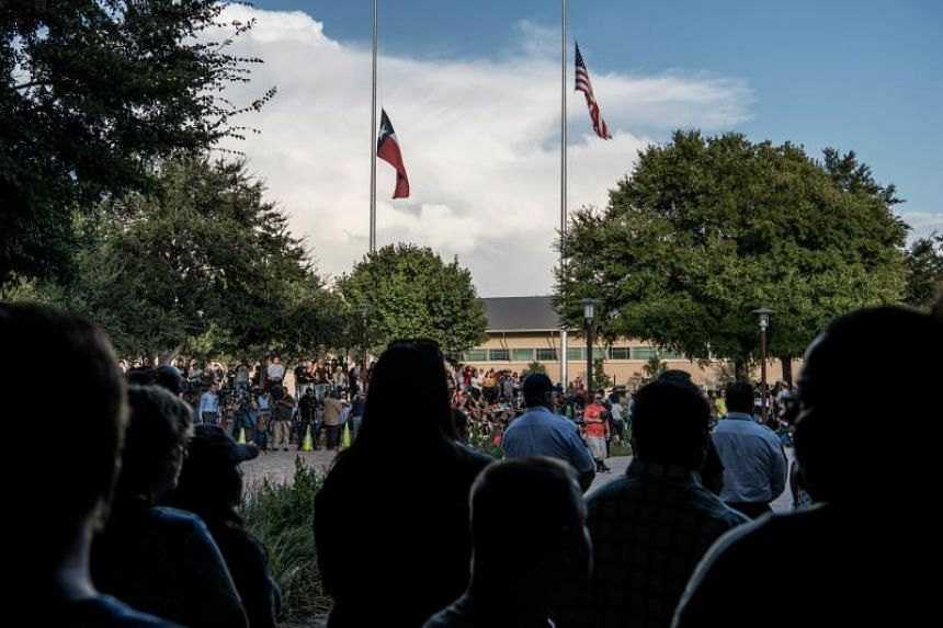 Flags fly at half-mast on Sept 1 over a prayer vigil at the University of Texas of the Permian Basin for the victims of a mass shooting on Aug 31.